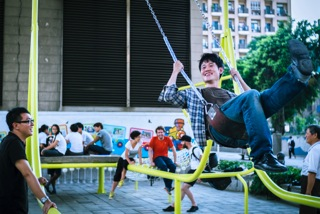 5. A young visitor to the Civil Swings Experimental Base on Aug. 10 tries to swing higher as his friend and members of Basurama lookon. (Photo courtesy of DOCA).