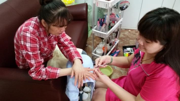 新移民阮春莊(右)細心的幫客人做指甲彩繪