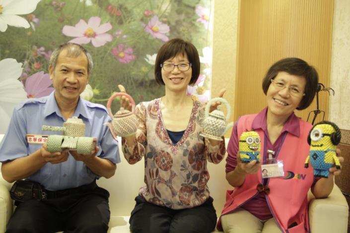 照片-蘇素珍區長(中)、志工林守妙(右)及保全張義郎愉快的展示精巧的紙藝作品