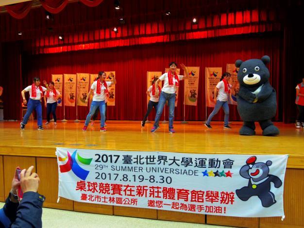 """由士林區公所同仁組成的舞團與""""熊讚""""一起跳世大運主題曲〈擁抱世界擁抱你〉舞蹈"""