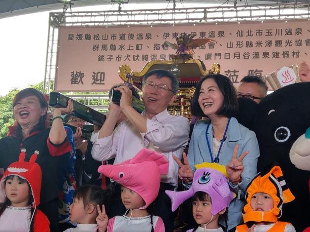 柯文哲市長(中)及臺北市溫泉發展協會周水美理事長(左)等貴賓一起抬神轎預祝溫泉季順利圓滿成功[開啟新連結]
