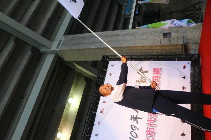 李再立局長接旗後揮舞旗幟為本市代表隊加油