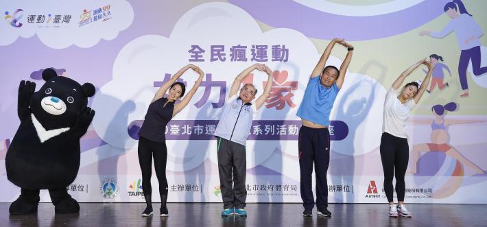 熊讚(左1)、瑜珈老師李詹瑩(左2)、體育署全民組呂組長忠仁(左3)、臺北市體育局李局長再立(右2)及空手道國手文姿云(右1)共同進行上肢伸展運動