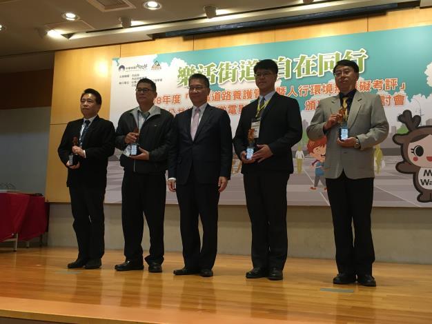 圖1. 內政部徐部長國勇頒發獎座,新工處張副總工程司泰昌代表領獎。