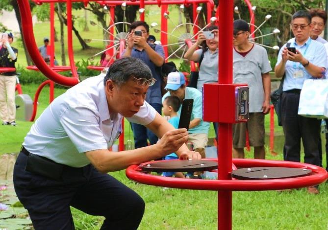 圖4.露出專心神情的柯市長正在研究活水飛輪互動遊戲平台[開啟新連結]