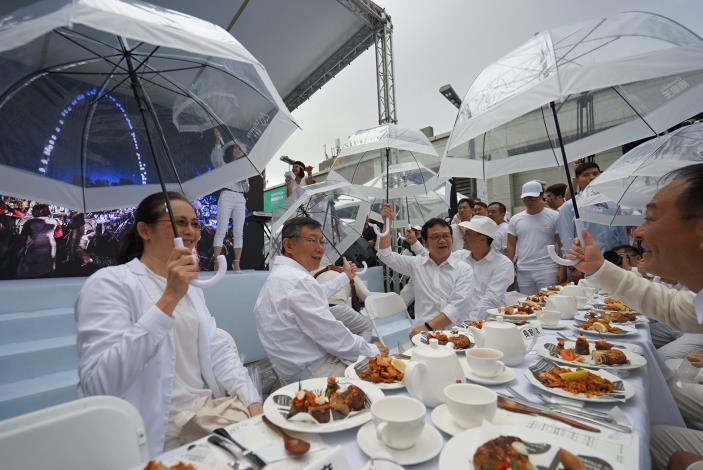 照片5.全場共同舉起雨傘紀念去年北門第一場白色野餐[開啟新連結]