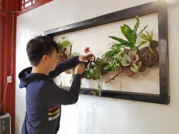 圖2.黃楚先生正進行新蘭亭入口籐球組合的製作(照片出自錫瑠環境綠化基金會)