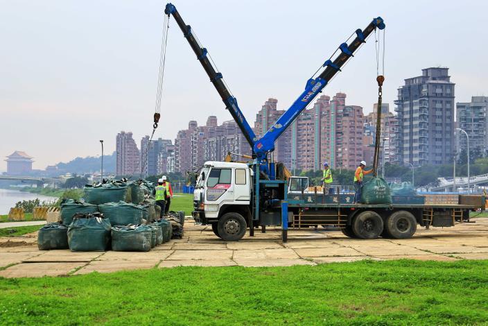 模擬堤防缺口搶修,出動2輛吊卡車和大卡車,載運250個超過30公斤的砂包[開啟新連結]