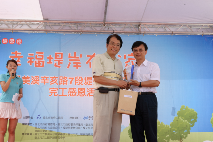 臺北市政府工務局局長致禮予實踐國小校長(Commissioner Lee of Public Works Department presents the Principal of Shi-Jian Elementary School an award of appreciation.)