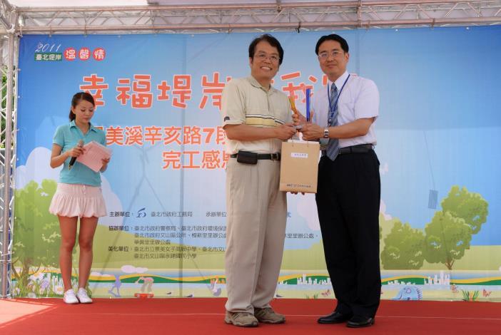 臺北市政府工務局局長致禮予永建國小校長(Commissioner Lee of Public Works Department presents the Principal of Yongjian Elementary School an award of appreciation.)