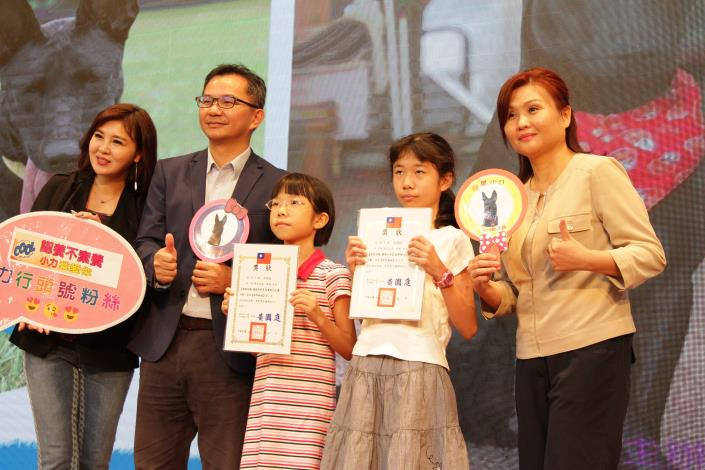 圖9.產業局吳副局長頒發獎狀給徵文比賽高年級得獎學生