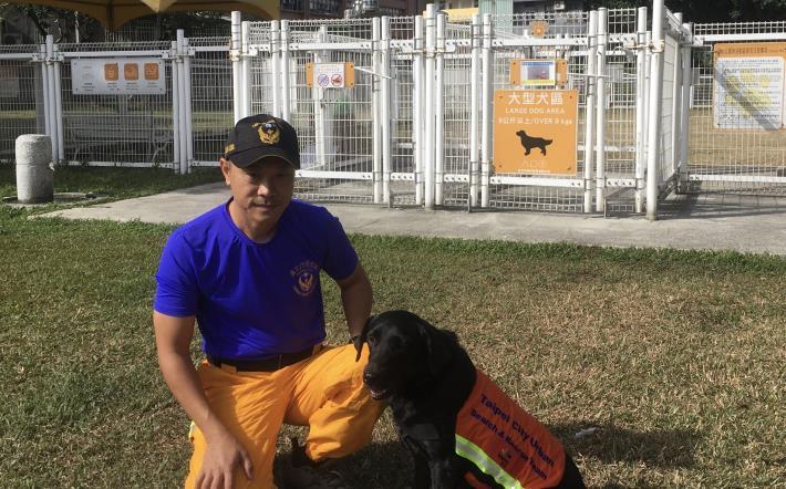 北市消防局搜救犬EVA和領犬員鍾金龍一同體驗臺北市各項動物友善設施。