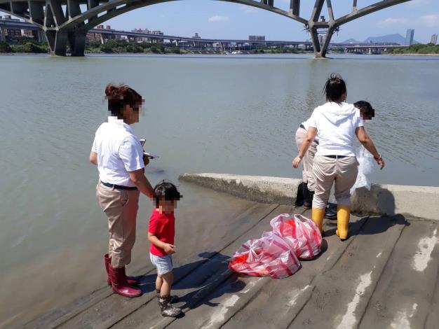 圖1.放生者一家以塑膠袋盛裝動物,準備於河濱公園放生。