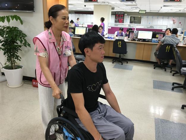 志工協助身障朋友至櫃檯[開啟新連結]