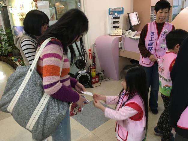 小志工雙手遞送號碼牌給民眾