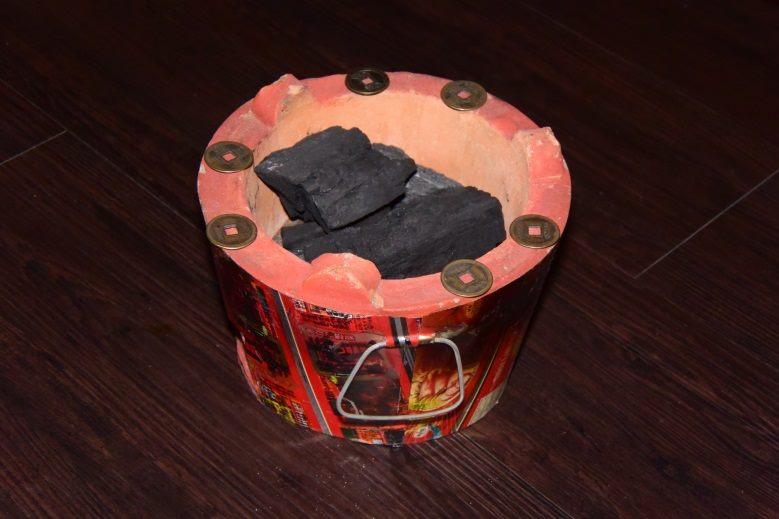圍爐桌下設一烘爐,爐中有炭,爐的周圍擺上五帝厭勝錢,有興旺富裕之意(李秀娥攝)