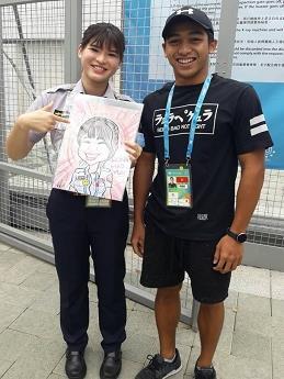 卡力與女警拿著Q版畫像在選手村安檢點前留下了值得紀念的合照(001).jpg