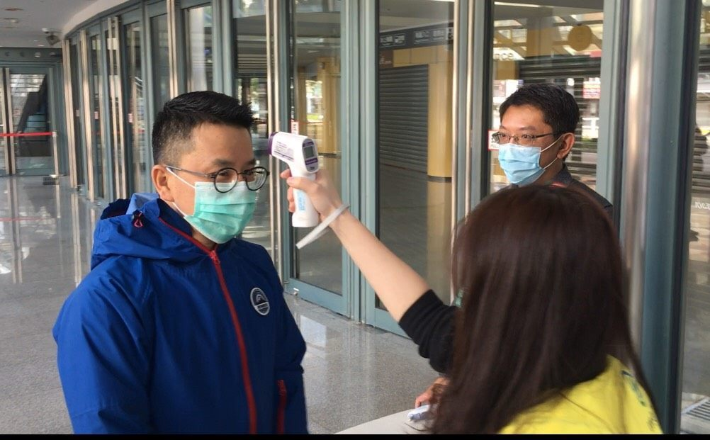 Staff takes the temperature of a visitor at the entrance of Taipei Arena