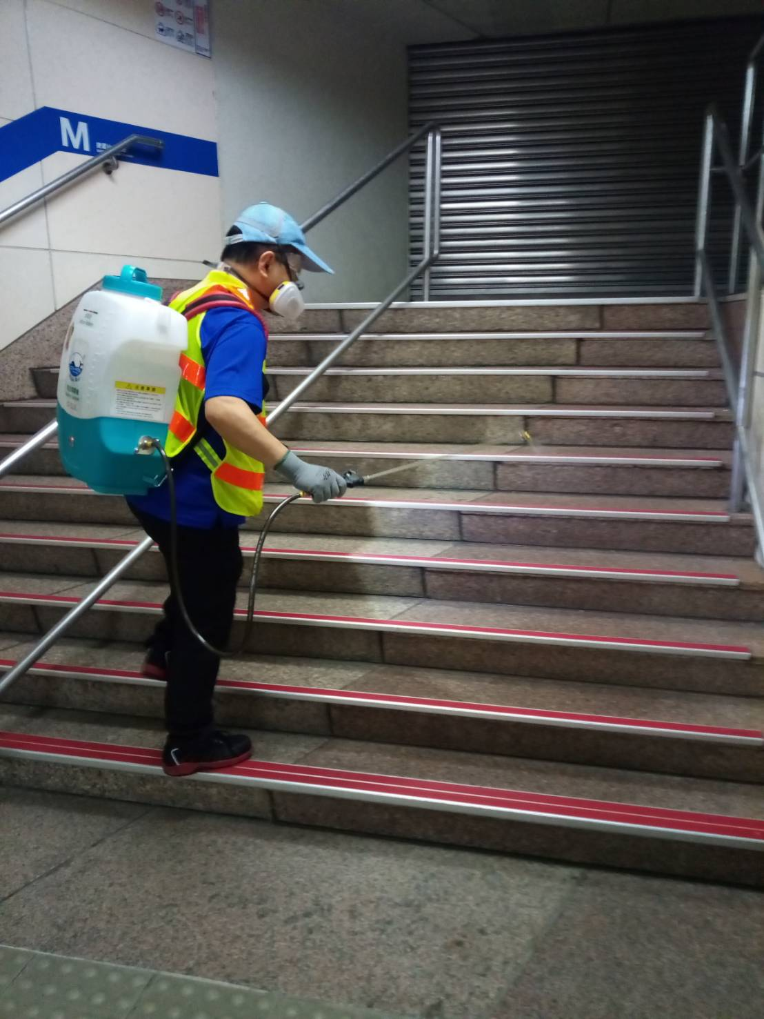 A worker disinfects the staircase at one of the MRT stations