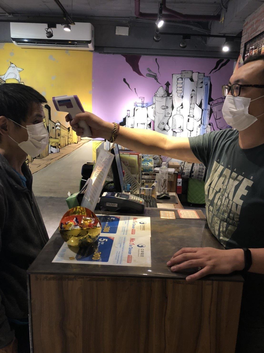Hotel worker at quarantine hotel checks guest's temperature