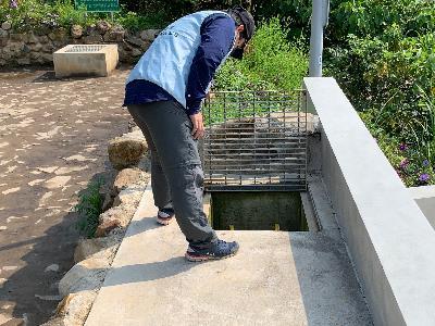 An expert inspects a deposit pond