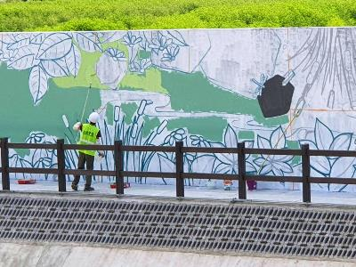An artist working on the mural at the riverside