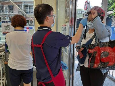 Supermarket staff taking the temperature of visitors