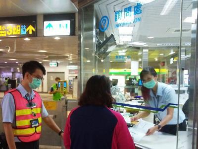 Staff and passenger in front of a MRT information booth