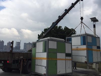 Cranes removing temporary restrooms at riverside park