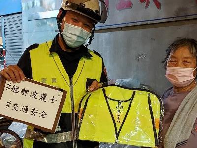 Police officers presenting a reflective vest to a local senior citizen.