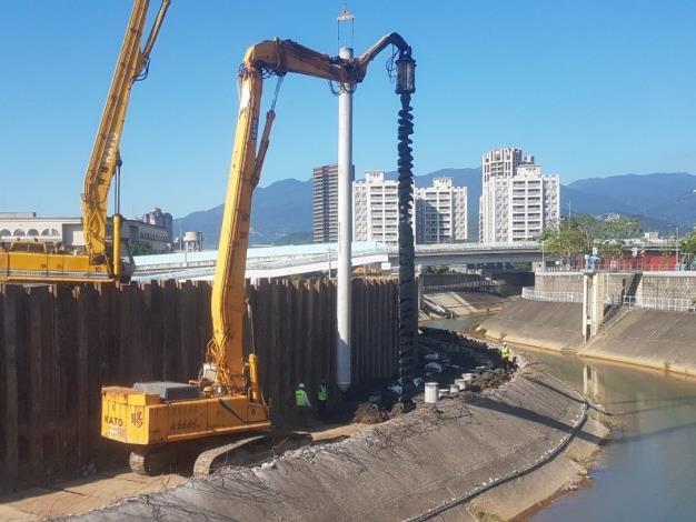 水利處的施工團隊施作防止沉陷的基樁並且築新堤