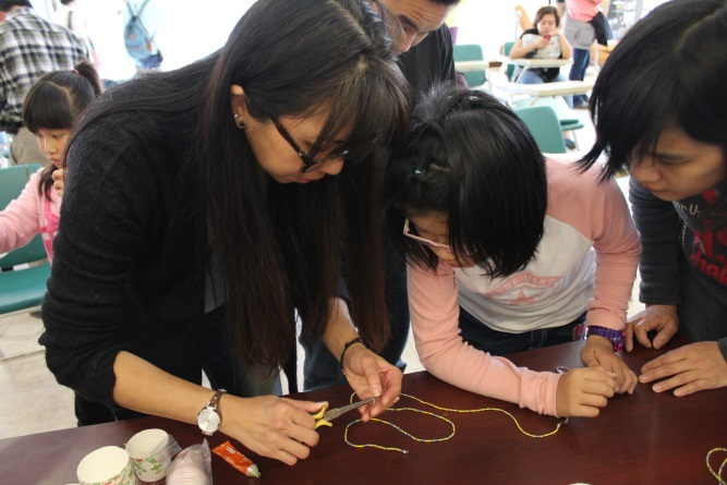 講師協助學員製作串珠手鍊