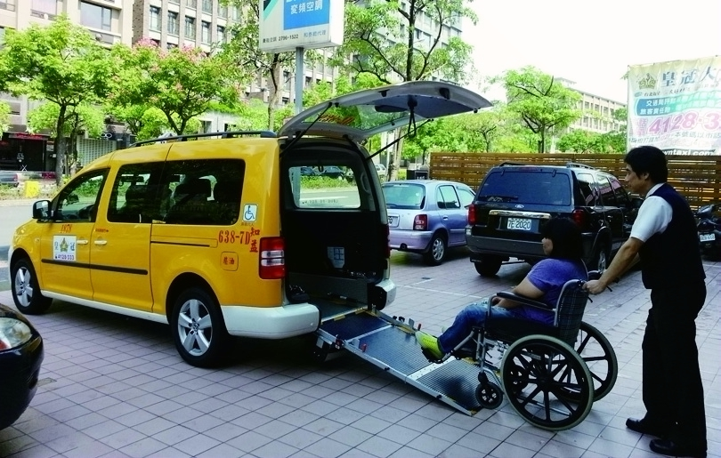 Assisting the people board a wheelchair-accessible taxi