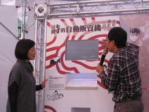 "Cheng Mei-hua (left), Director of the Taipei Department of Cultural Affairs, and Hung Hung (right), one of the curators for the Taipei Poetry Festival, demonstrate how to use the ""Automatic Vending Machine of Poetry"" at the Thursday press conference in Taipei. (Photo by Yali Chen / Taiwan News)"
