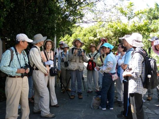 Mr. Chen teaching volunteers the proper way of using binoculars to study birds