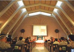 2. The high-ceilinged assembly hall at Grace Baptist Church, with its raised altar and large wooden cross on the wall behind, has an air of solemn majesty.
