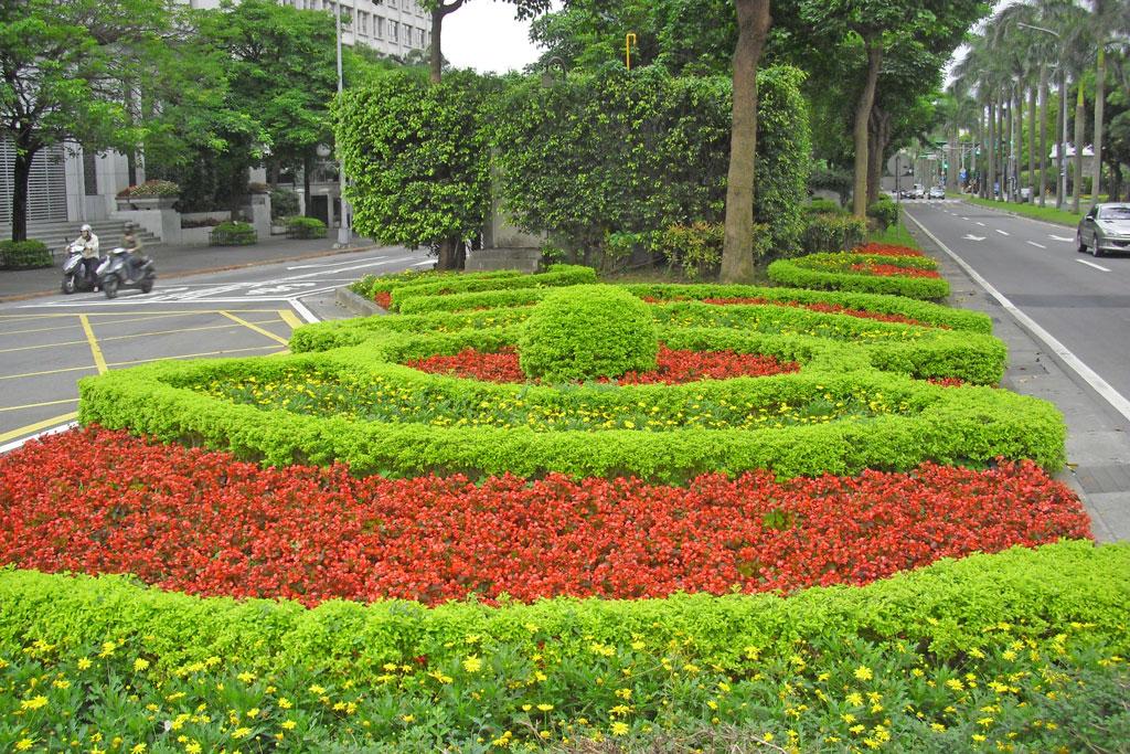 愛國西路中央分隔島以顏色對比之草花搭配造型灌木型塑視覺焦點