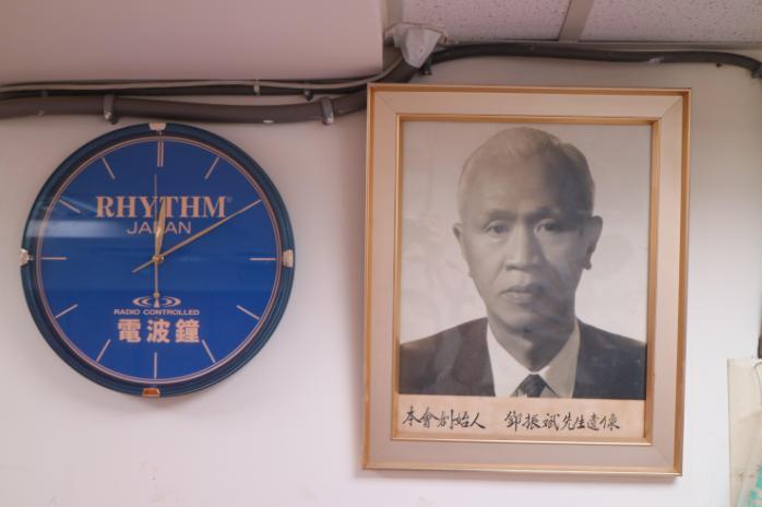 綽號「白毛仔」的鄧振斌,是工會創始人,也是促使工會發展的靈魂人物。鐘錶工會辦公室高高掛著創會長鄧振斌的照片,與一只日本麗聲品牌早期生產的電波鐘。(照片提供/邱秉儀)