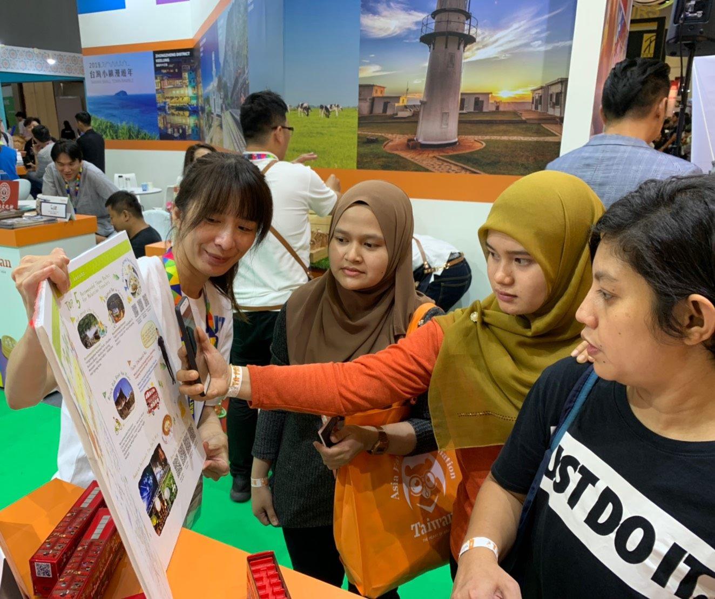 穆斯林民眾在臺北展攤專注聆聽,拿起手機掃瞄臺北旅遊網QR-code