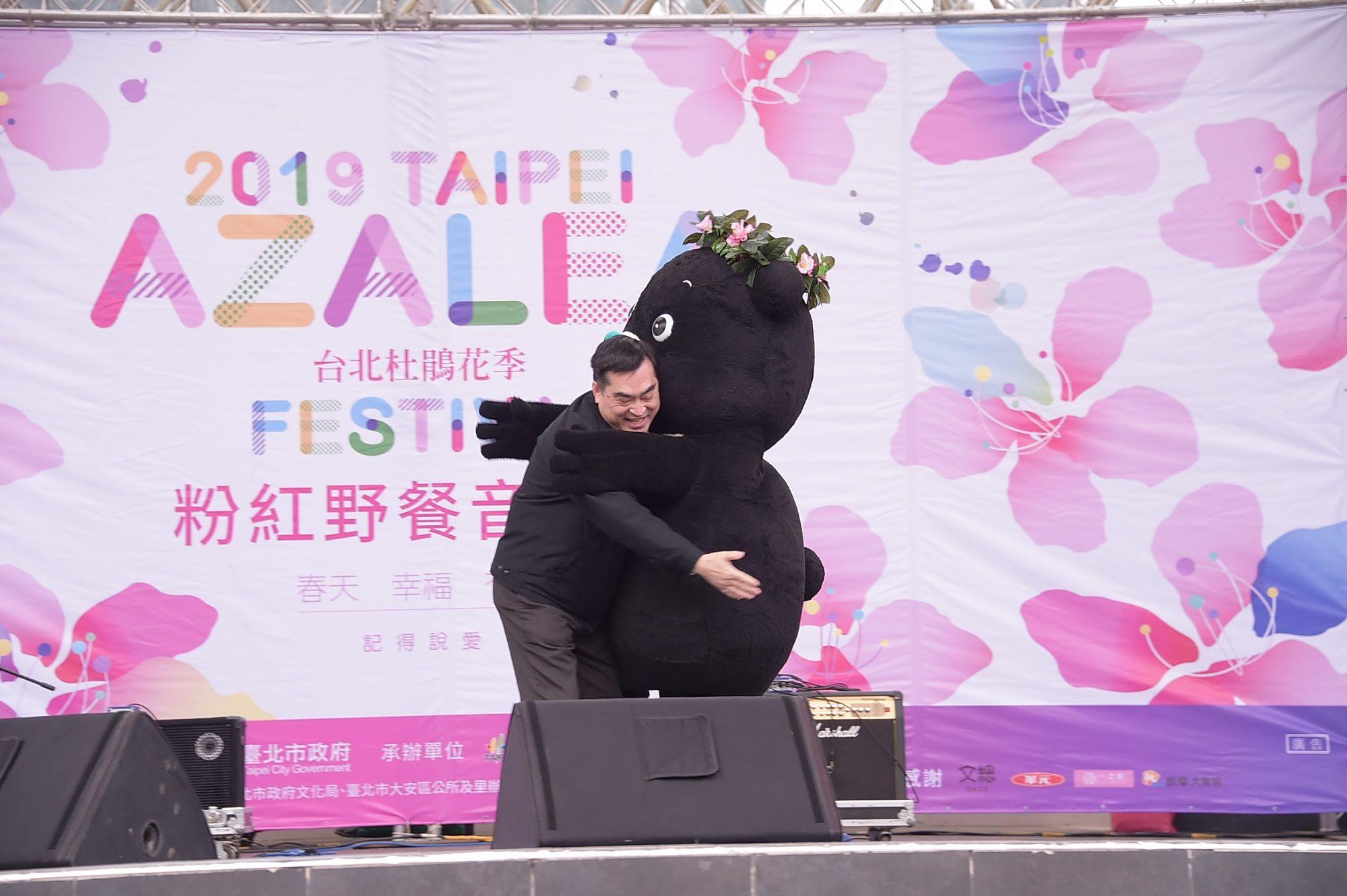 熊讚頭戴花圈與鄧家基副市長擁抱,熱情滿滿~