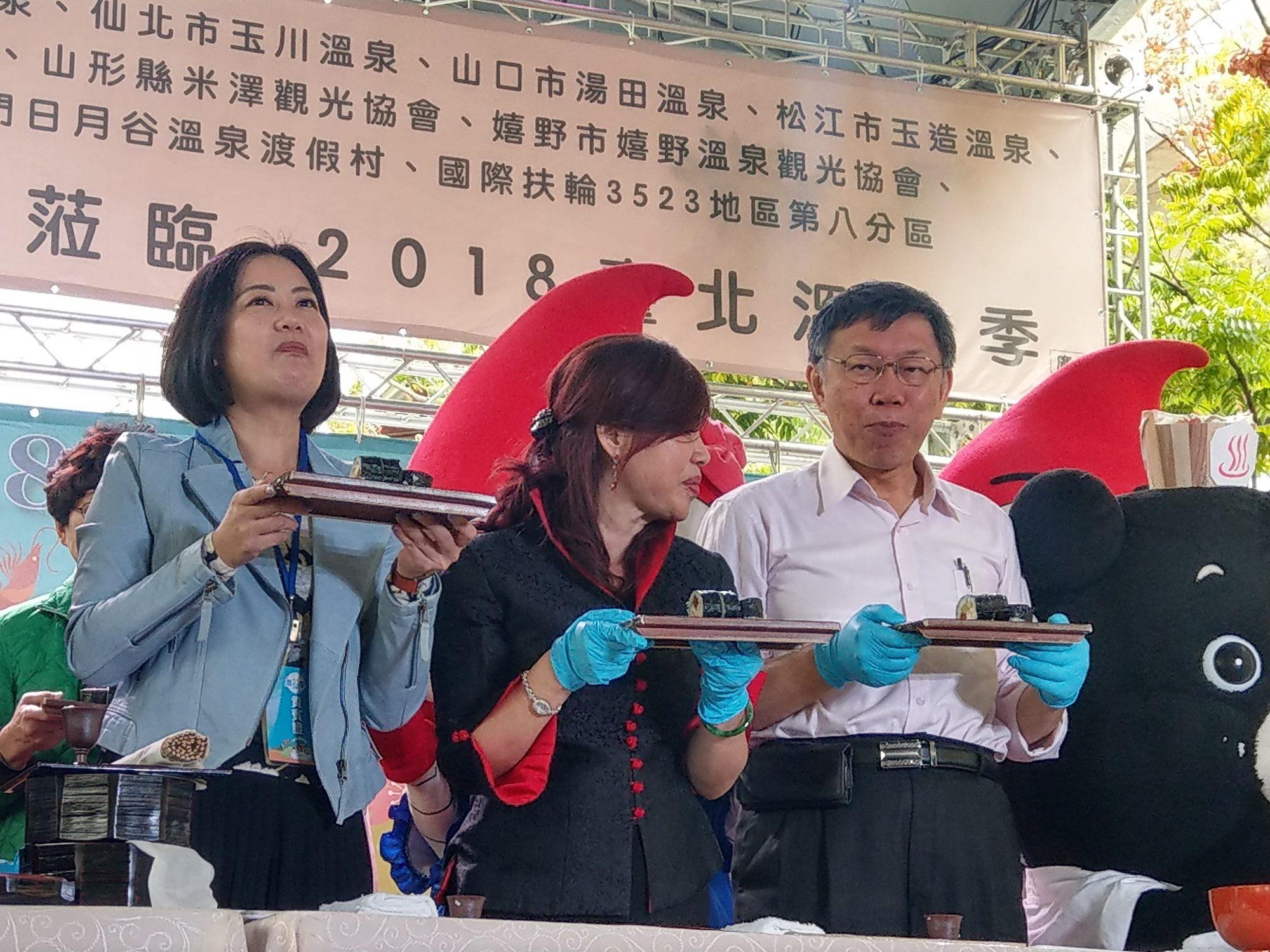 柯市長(右)及臺北市溫泉發展協會周水美理事長(中)等貴賓一起手作海灣料理『北投捲』
