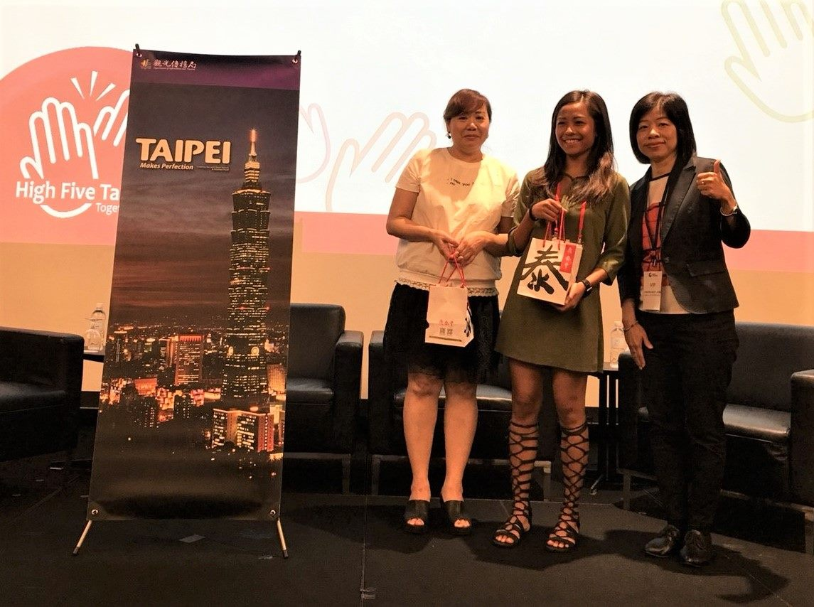 Lucky agents at Singapore promotion event presented with gift sets containing chili sauce from Taipei Din Tai Fung and Taipei Double-Decker Sightseeing Bus tickets, happily posing for a group photo with Taipei City DOIT's representative.