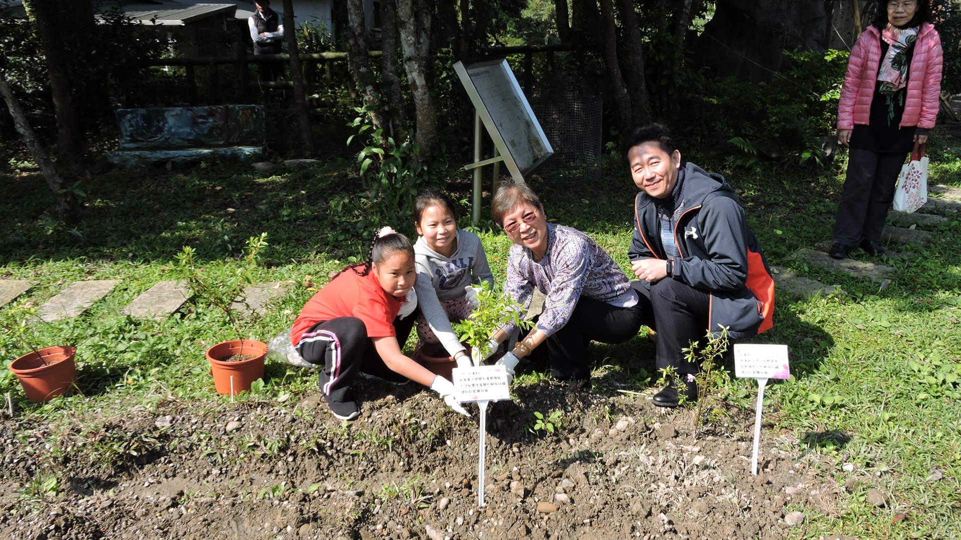 圖說:余主任秘書星華與龜山國小李校長正琳、同學們一同種植烏來杜鵑幼苗。