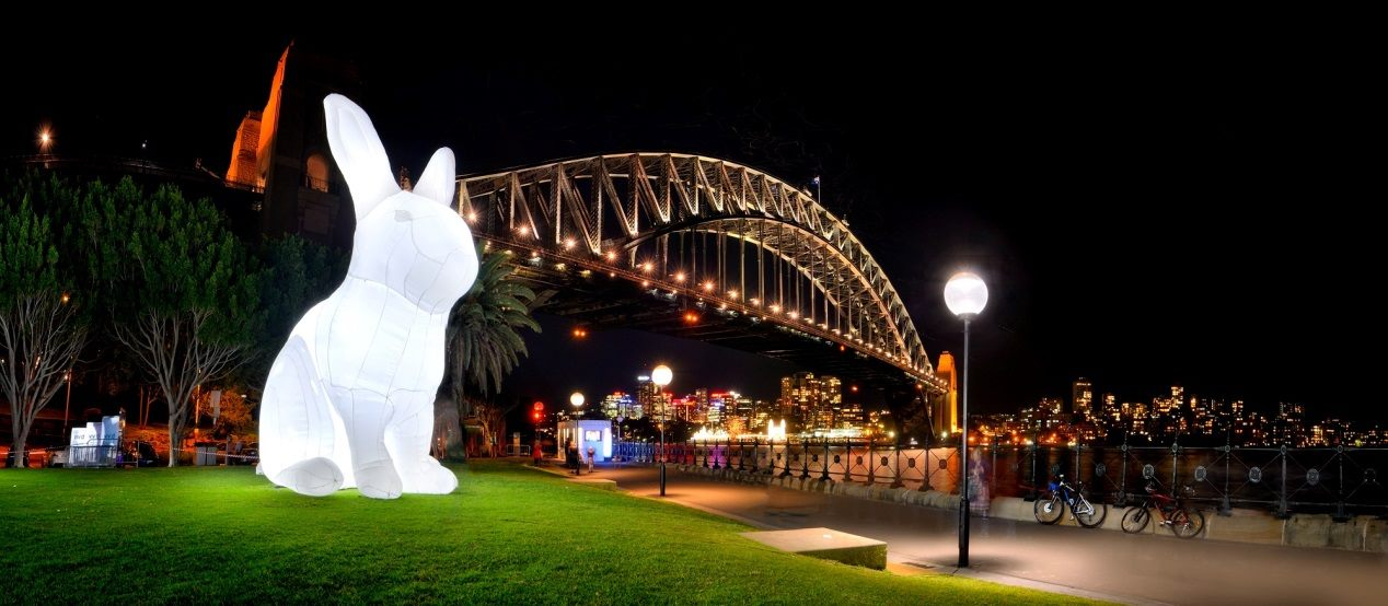 """Illuminated in stark white light, """"Intrude"""" is a 7-meter-tall inflatable white rabbit."""