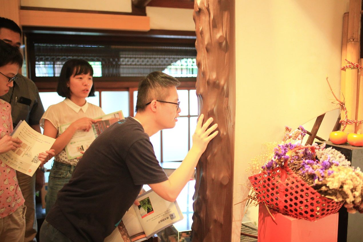 One young man with a learning disability touches a wooden pillar of the Kishu An Forest of Literature in Taipei.