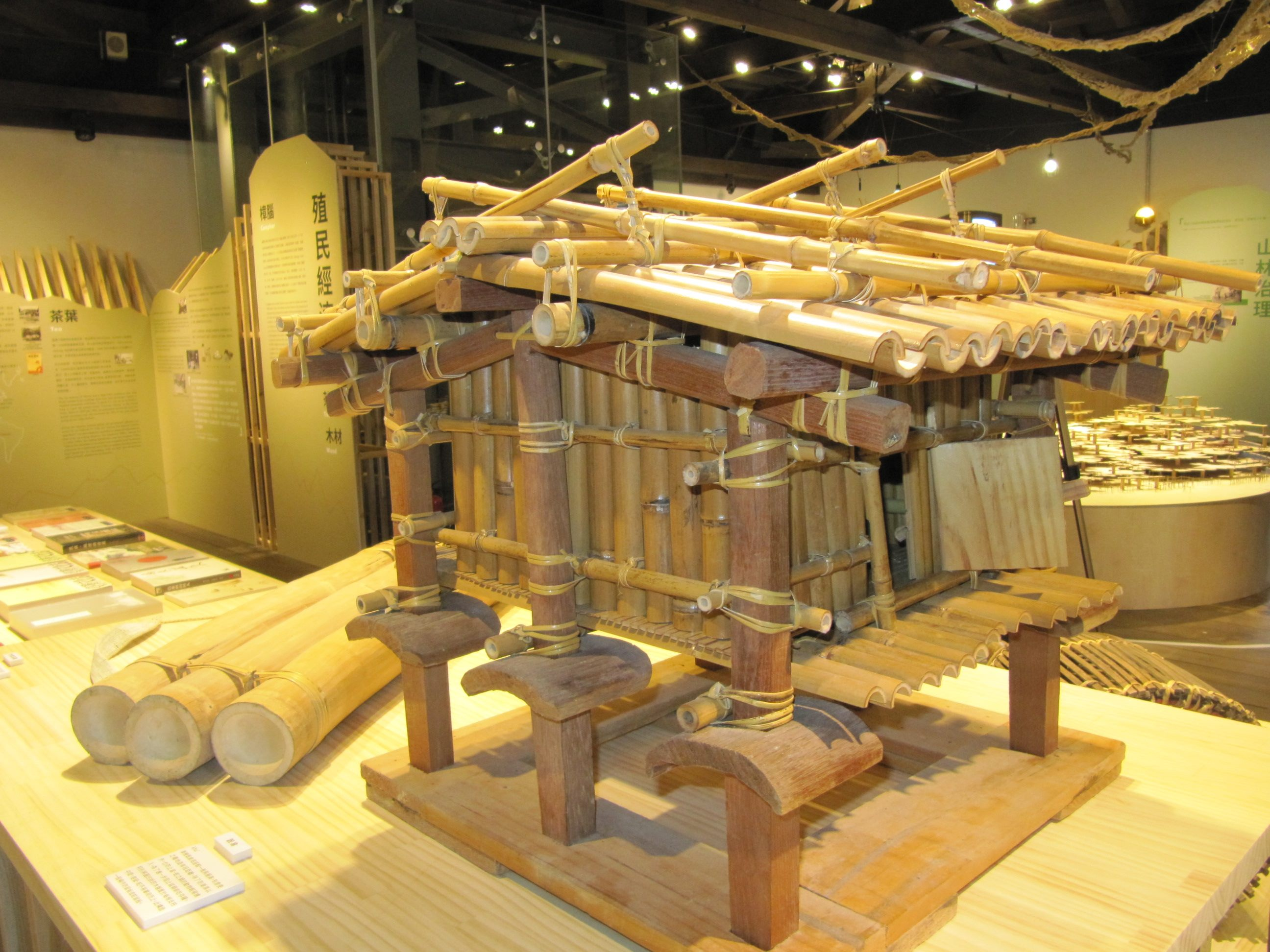 A model of the Atayal traditional barn and three bamboo water bottles
