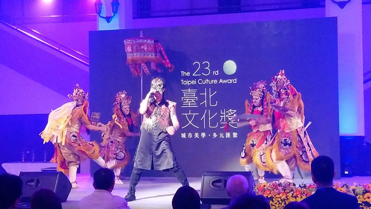 The Chairman's vocalist sings Taiwanese rock music while a traditional martial arts team performs their wushu moves.