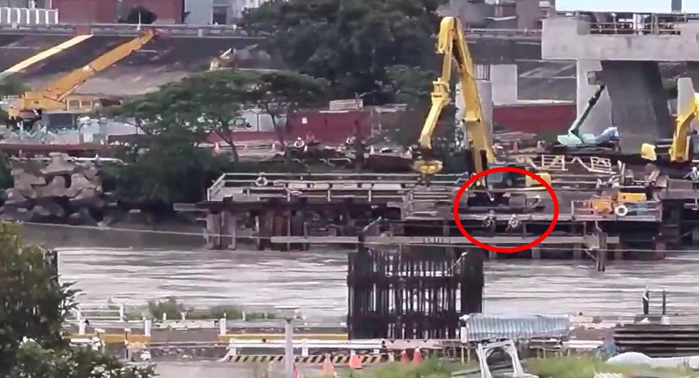 兩名勞工於施工便橋鋼樑上進行放樣作業