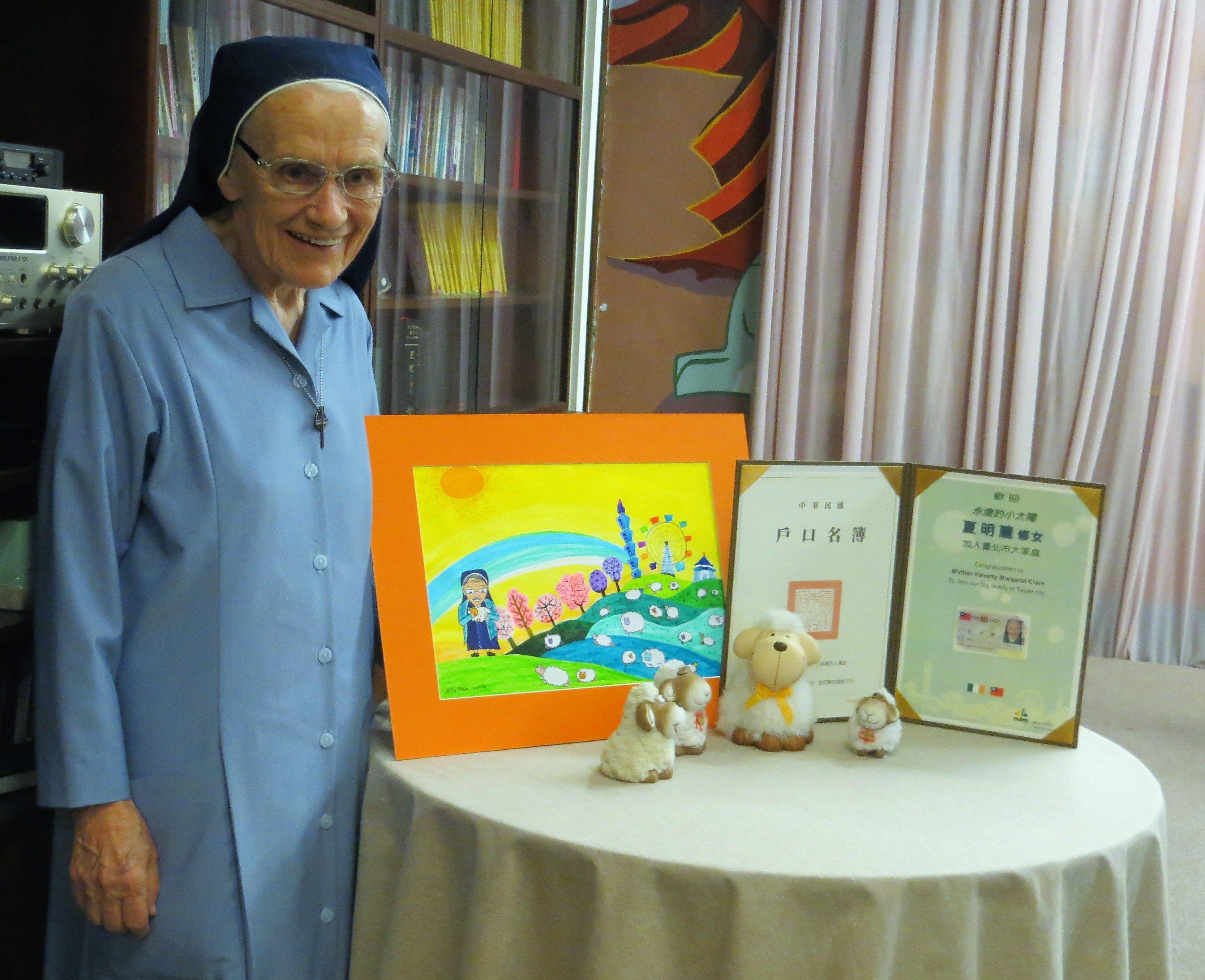 9 夏修女開心和身分證、戶口名簿及市府致贈的小禮物合照
