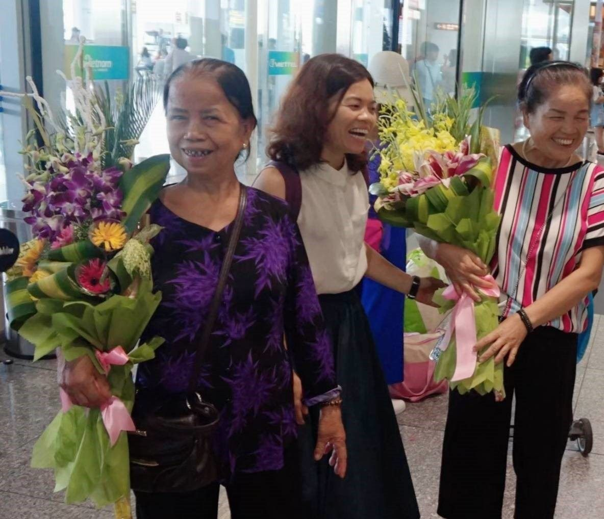 Vietnamese women smiling after receiving flowers for the Vietnamese Women's Day